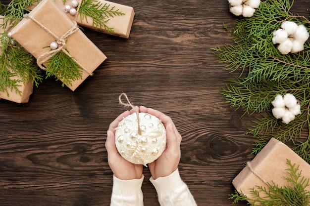 Женские руки держат елочный шар на фоне подарочных коробок и еловых шишек
