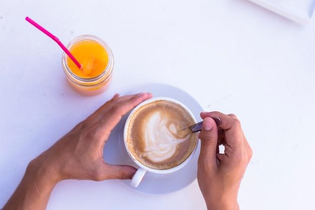 ほかにコーヒー、オレンジジュースのカップを保持している女性の手。健康的な朝食。上面図