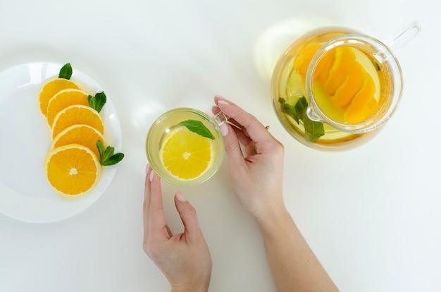 白い背景の上のオレンジ色の果物とミントのデトックス紅茶のカップを保持している女性の手。