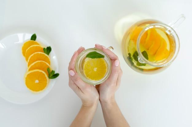 オレンジ色の果物と白の背景にミントのデトックス紅茶のカップを保持している女性の手。