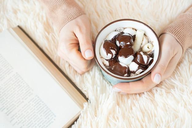 柔らかい毛布の上においしいコーヒーのカップを保持している女性の手。本は近くにあります。居心地の良い家庭的な雰囲気。本の中のテキストは認識できません。