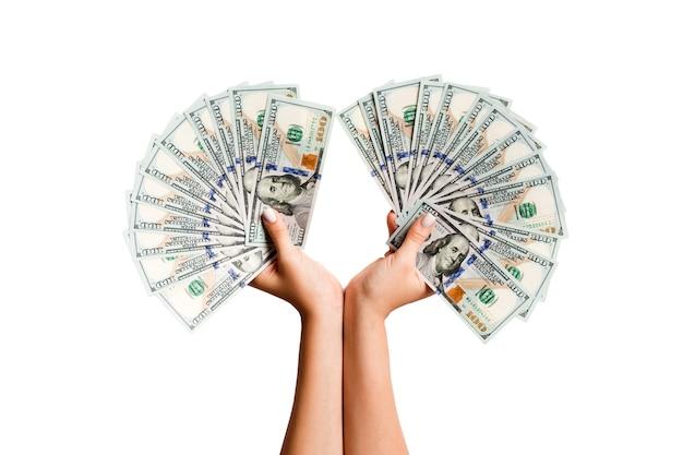 Женские руки, держа веер долларовых банкнот на изолированном фоне. успех и инвестиционная концепция.