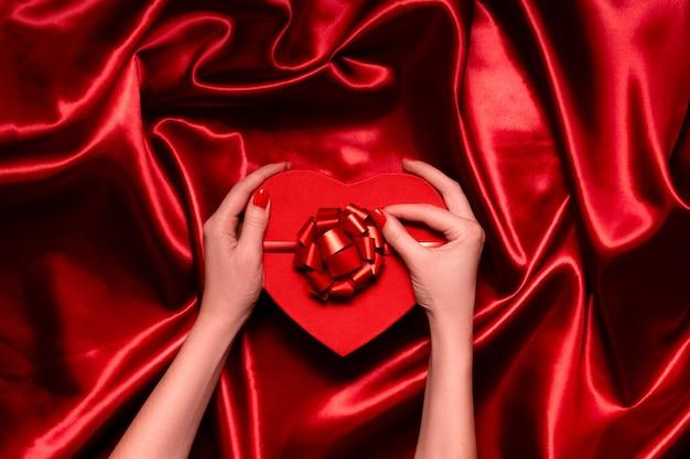 Женские руки держат праздничную коробку с лентами и бантами. красный праздничный фон copyspace горизонтальный вид сверху.