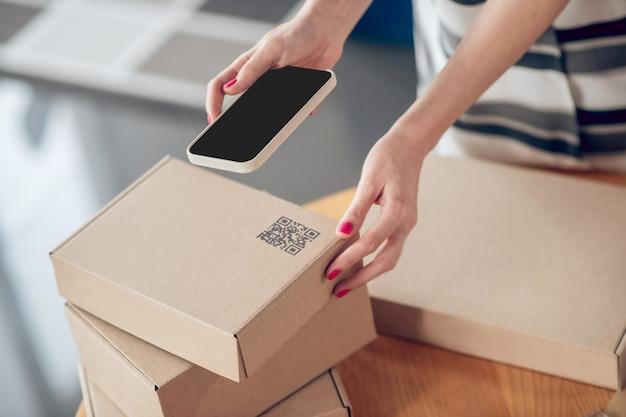 Женские руки держат гаджет над упакованной коробкой