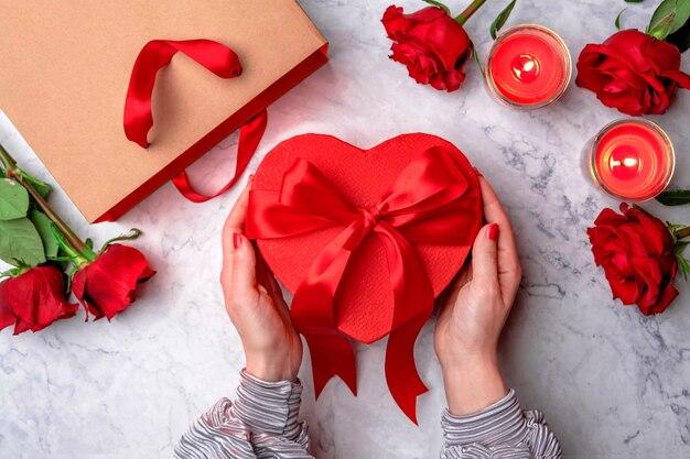 バラに囲まれたサテンの弓とギフトの赤いハート型のボックスを保持している女性の手