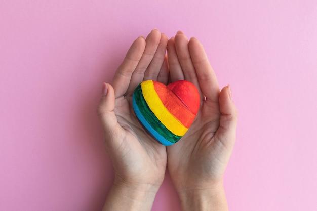 Женские руки, держа сердце в цветах лгбт, концепция свободной любви.