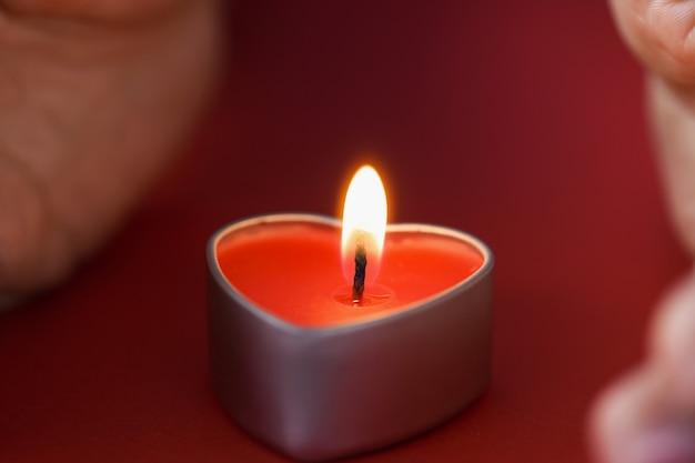 어두운 밤 촛불 점 개념에서 심장 모양의 촛불을 들고 여성 손