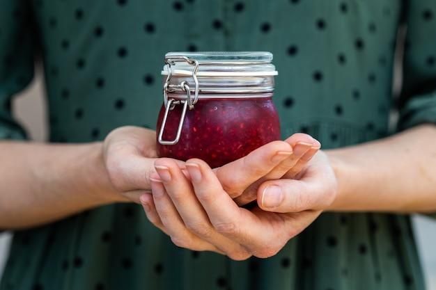 Женские руки держат домашнее веганское сырое малиновое варенье в стеклянной банке