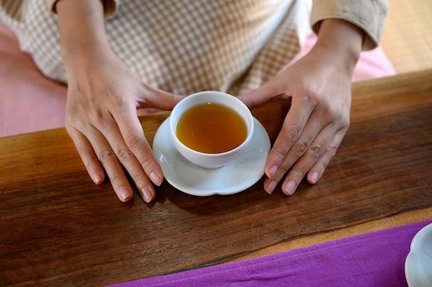 朝、木製のテーブルに熱いお茶を持っている女性の手