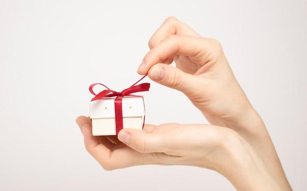 豪華な小さなギフトボックスを保持している女性の手。白い背景で隔離。クリスマスと元日。デザインの準備ができたテンプレートをモックアップします。