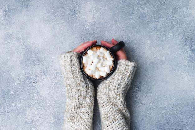 Женские руки держат кружку с горячим шоколадом и зефиром на сером