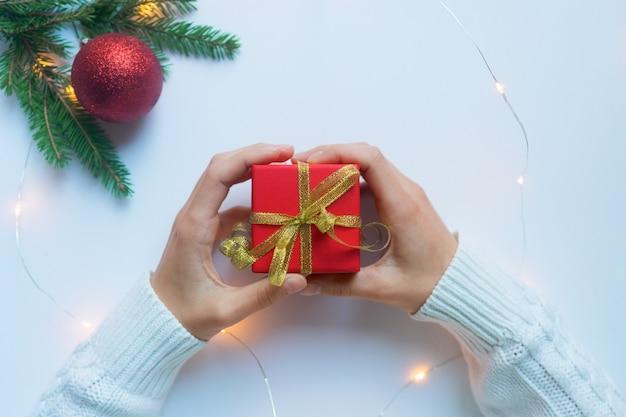 Женские руки держат красную подарочную коробку, перевязанную золотой лентой. концепция подарков на рождество и новый год.