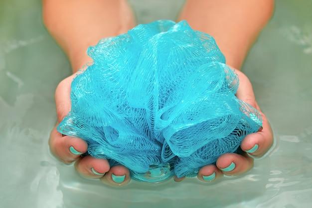 水とお風呂で丸い柔らかい合成手ぬぐいを保持している女性の手。手のクローズアップ。スパトリートメント、ボディケア、水の背景。