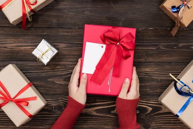 白いテーブル トップ ビューの冬のお祭りの装飾の中でギフトの小さな箱を保持している女性の手。誕生日、クリスマス、または結婚式用のフラット レイアウト構成。