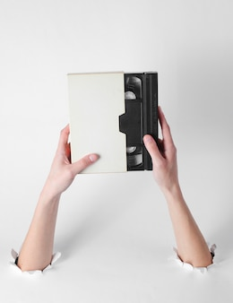 Женские руки держат видеокассету в футляре