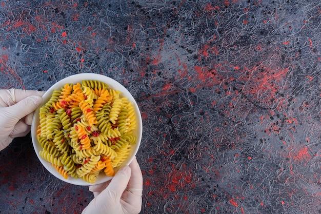 Женские руки держат белую тарелку сырых сухих разноцветных макарон фузилли на темной поверхности