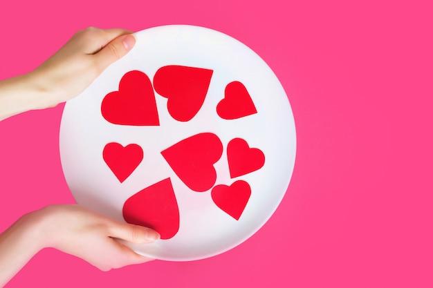 Женские руки держат белую тарелку с сердечками на розовом