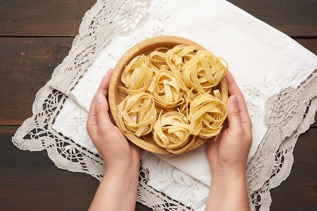 Женские руки держат деревянную тарелку с сырой пастой феттучини над деревянным столом