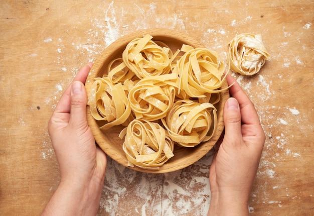 Женские руки держат деревянную тарелку с сырой пастой феттучини