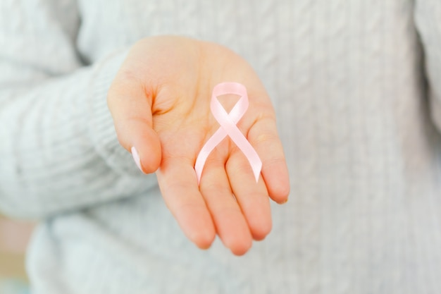 Female hands holding aids awareness ribbon