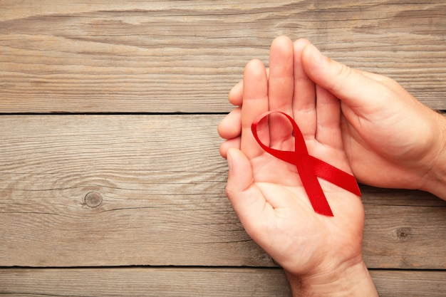 A female hands holding an aids red ribbon