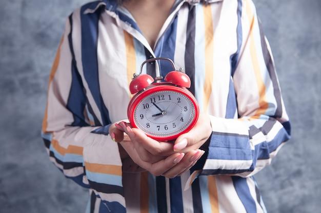 Female hands holding an alarm clock