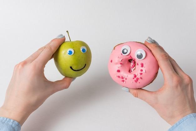큰 눈과 재미있는 얼굴을 가진 사과와 도넛을 들고 있는 여성의 손. 다이어트 개념입니다.