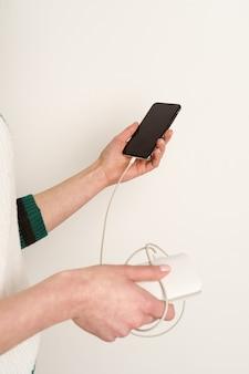 여성의 손을 잡고 전원 은행을 충전하는 동안 스마트 폰을 사용
