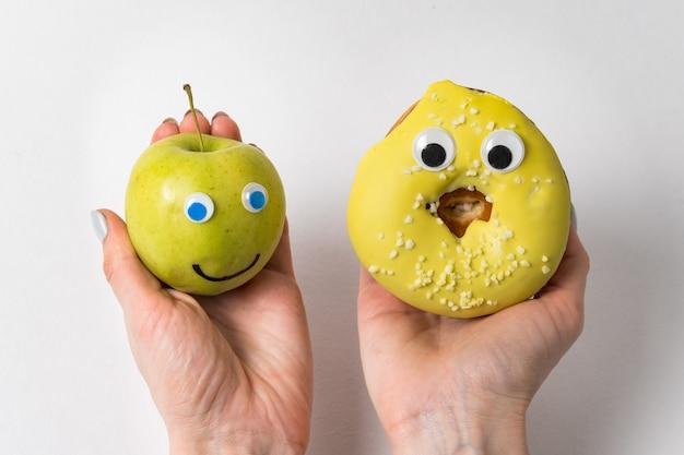 재미있는 얼굴과 거대한 눈을 가진 사과와 도넛을 들고 있는 여성의 손. 적절한 영양 개념.