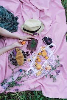 Женские руки держат фрукты абрикоса на розовом одеяле на траве, со свежими фруктами, ягодами и выпечкой на открытом воздухе