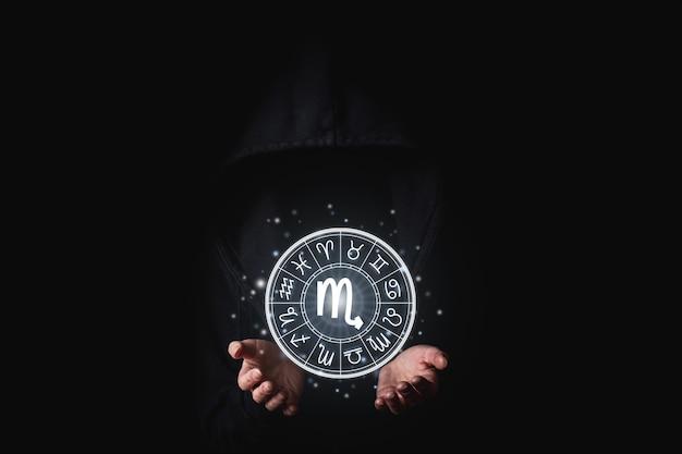 검정색 배경에 원 안에 조디악의 점성술 표지판을 들고 있는 여성의 손.