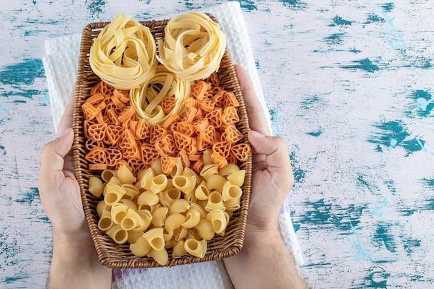 Mani femminili che tengono cesto di pasta secca.