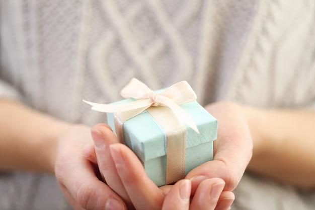 새틴 리본으로 싸인 아름다운 작은 선물을 들고 있는 여성의 손.