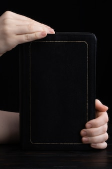 Female hands holding a bible on a dark background.