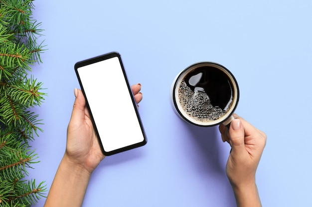 Female hands holding black mobile phone with blank white screen and mug of coffee