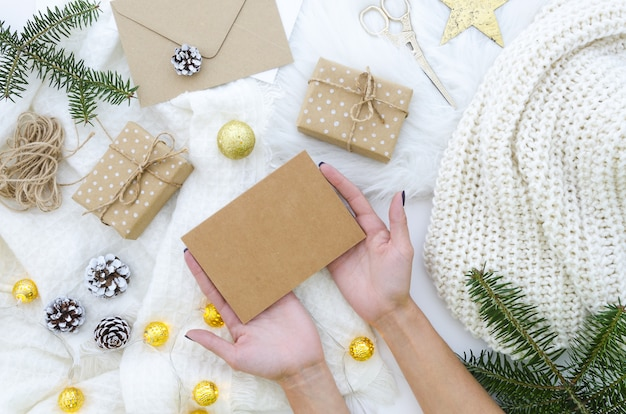 Female hands holding blank kraft paper mockup for merry christmas greeting card