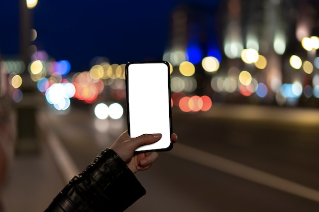 Female hands holding blank screen smartphone at street night in city.