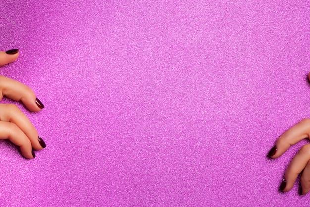Female hands holding blank shimmer violet paper background.