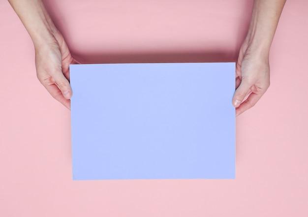 파란색 종이 시트를 들고 여성 손