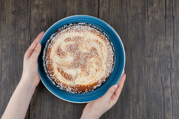 木製のテーブルの上に置かれたおいしいパイの青いプレートを保持している女性の手。