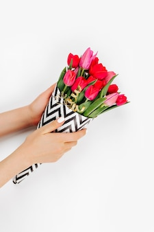 Female hands holding a bouquet of tulips wrapped in paper