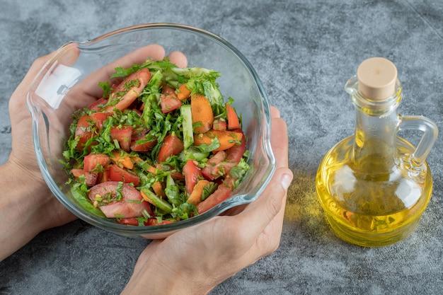 Mani femminili che tengono ciotola di insalata di verdure sulla superficie di marmo.