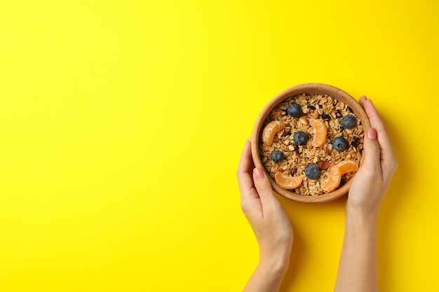 Female hands holding bowl with granola