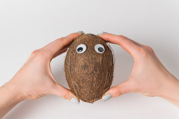 Female hands holding brown coconut on white background.