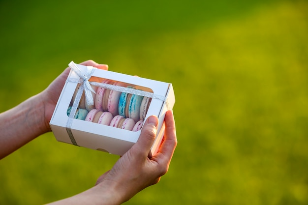 Female hands holding cardboard gift box with colorful pink blue handmade macaron cookies on green blurred