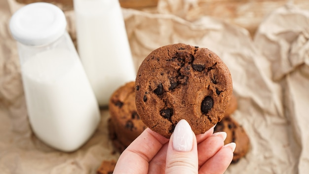 초콜릿 칩 쿠키를 들고 여성 손입니다. 선택적 초점입니다. 공예 종이에 우유와 쿠키