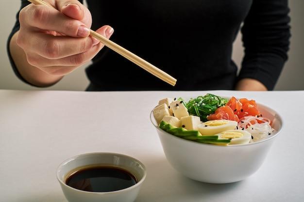 Female hands holding chopsticks poke bowl with salmon, avocado sesame soy sauce