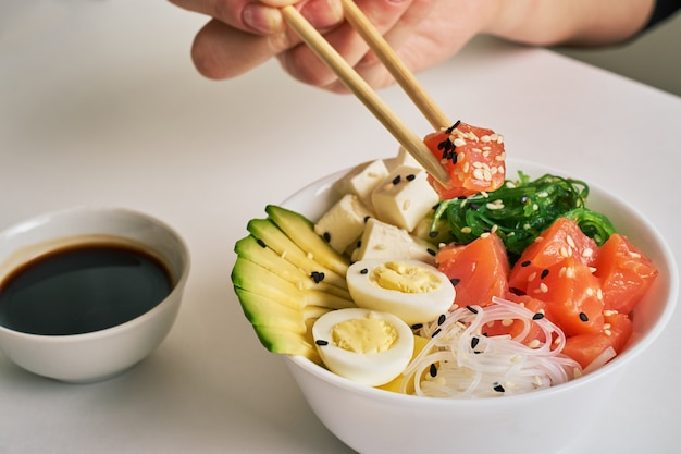 Female hands holding chopsticks poke bowl with salmon, avocado sesame soy sauce