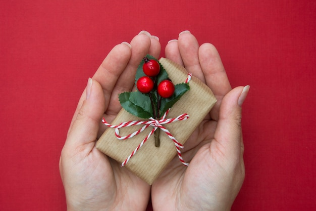 Female hands holding christmas gift box with red ribbon , over red background.