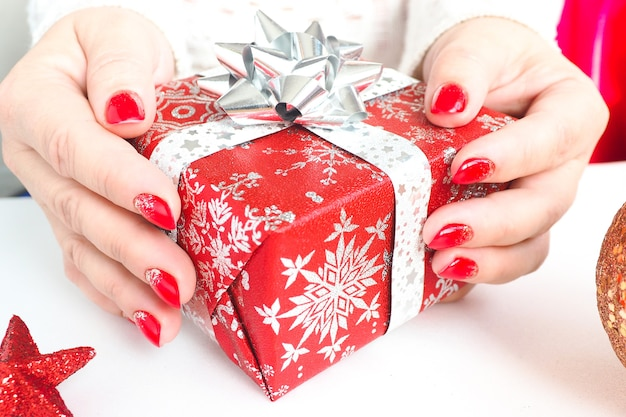 クリスマスプレゼントを持っている女性の手